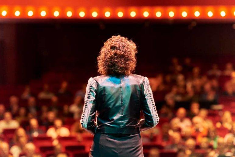Jolanda op het podium voor 300 mensen in de zaal