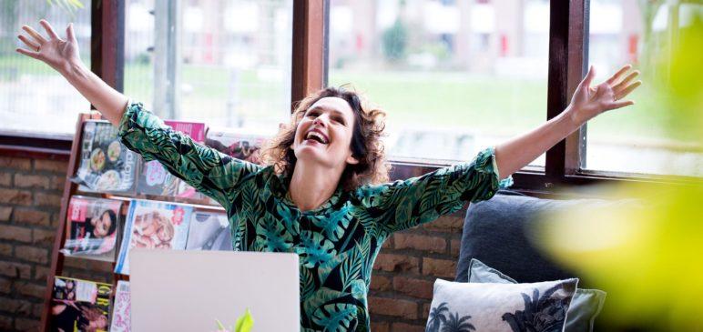 Een blije Jolanda achter haar laptop die een leuke mail van een klant krijgt
